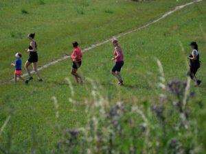 kobiety i dzieci bieglące przez łąkę parkową techniką slow jogging